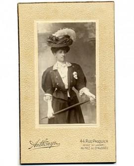 femme élégante, en chapeau à plumes, une canne à la main