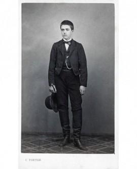 Jeune homme posant debout tenant un chapeau melon