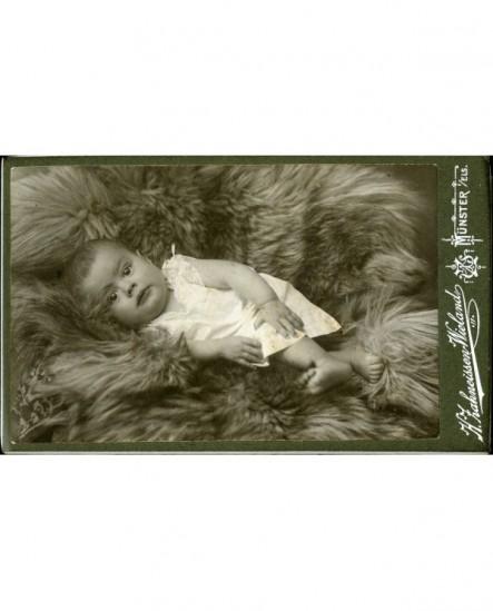 Bébé en chemise, allongé sur une fourrure