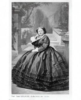 Femme en robe posant assise. Mme Marey Monge