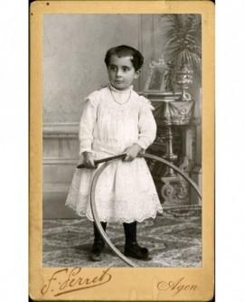 Enfant en robe blanche avec cerceau (jouet)