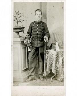 Militaire avec trompette, main sur son sabre, shako près de lui