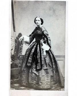 Femme en robe debout appuyée à une chaise