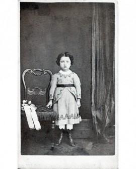 Enfant debout à côté d'une chaise avec deux poupées. jouet