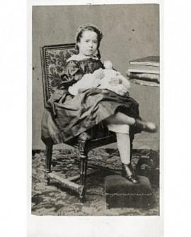 Petite fille assise sur une chaise avec une poupée dans les bras