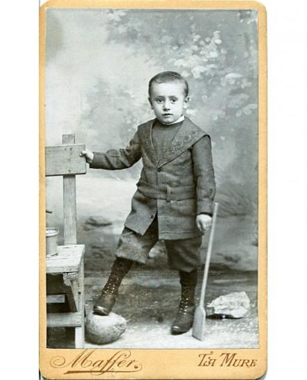 Enfant debout avec pelle et seau (jouet)
