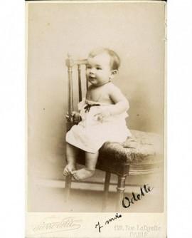 Bébé en chemise, épaules dénudées, assis sur une chaise
