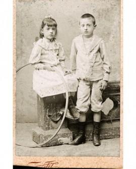 Frère debout et soeur assise, tenant baguette et cerceau