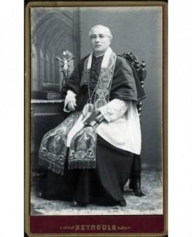 Prêtre posant assis en grande tenue