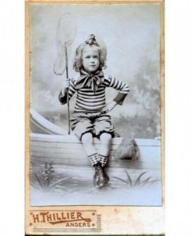 Enfant en veste de marin tenant un filet à crevettes. jouet
