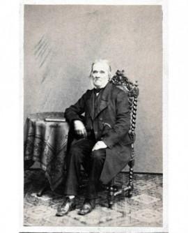 Homme agé assis devant un livre. M. Multier