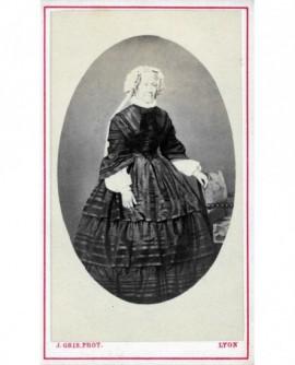 Femme en robe posant debout appuyée à une chaise