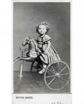 Enfant en robe assis sur un cheval tricycle (jouet)