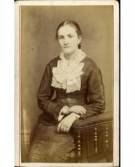 Femme au jabot de dentelle assise, mains croisées
