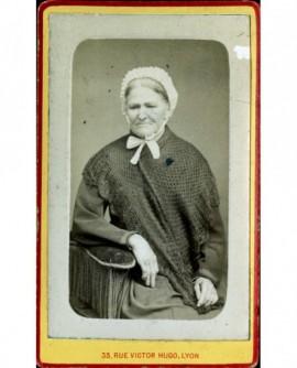 Femme âgée en coiffe, assise, tricot sur les épaules