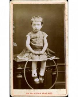 Petite fille assise sur une table, tenant un cerceau (jouet)