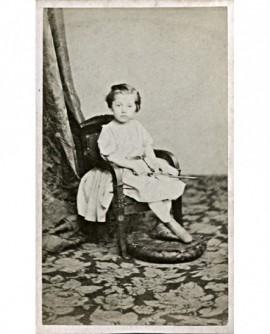 Fillette assise sur un petit fauteuil, diabolo à la main (jouet)