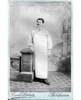 Homme posant debout avec tablier de boucher