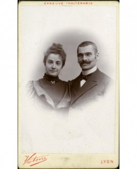 Couple souriant: homme moustachu à lorgons, femme en col roulé