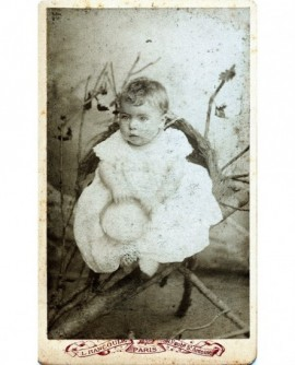 Bébé en robe assis tenant un chapeau
