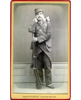 Militaire debout avec son fusil et son sac sur le dos