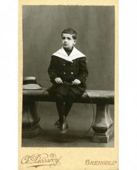 Petit garçon en marin tenant un cerceau (jouet)