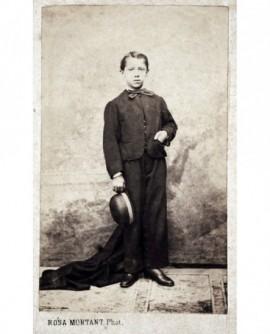 Jeune garçon debout chapeau en main