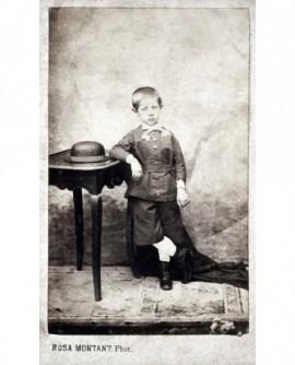 Jeune garçon debout accoudé, chapeau sur une table