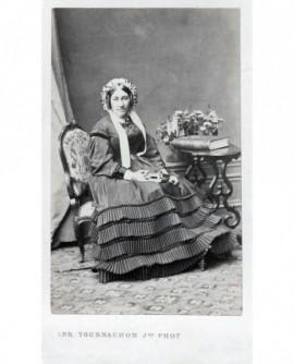 Femme en robe portant une charlotte posant assise