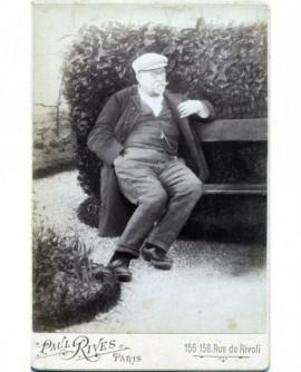 Homme agé moustachu assis sur un banc