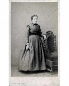 Jeune femme debout accoudée à une chaise