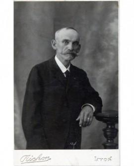 Homme agé moustachu posant accoudé à une sellette