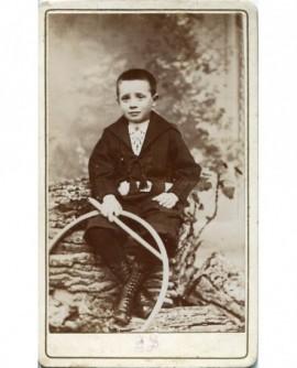 Enfant assis tenant un cerceau (jouet)