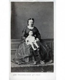 Femme en grande robe présentant un bébé