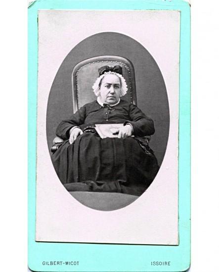 Femme agée assise portant une charlotte