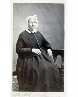 Femme posant assise portant une charlotte
