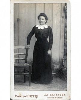 Femme en robe noire debout appuyée à une chaise