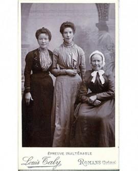 Deux jeunes femmes et une femme agée posant