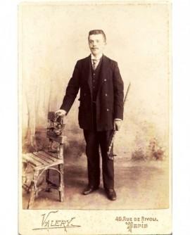 Jeune homme moustachu debout, canne à la main, appuyé à une chaise