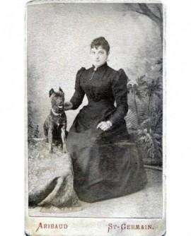 Femme en robe assise posant avec un chien. Marie Caiplet