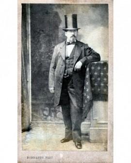 Homme debout en costume et haut de forme