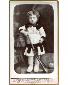 Enfant en robe debout tenant une carabine. jouet