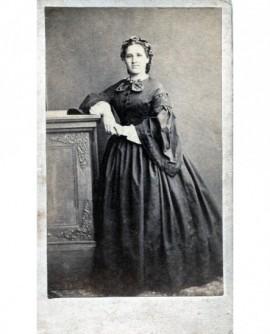 Femme debout en robe posant accoudée