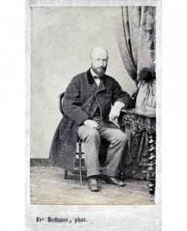 Homme en manteau posant assis