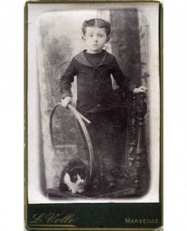Enfant debout avec cerceau et un chat (jouet)