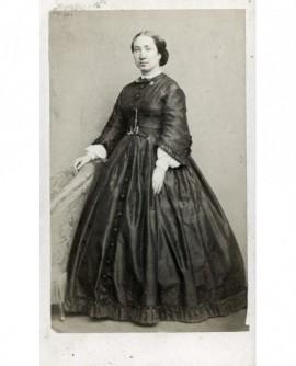 Femme en robe à panier appuyée sur un fauteuil