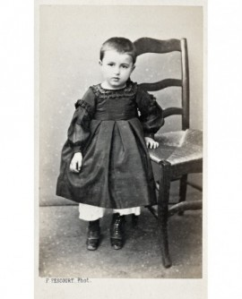 Jeune enfant en robe appuyé à une chaise