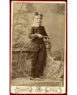 Petit garçon sur un banc de pierre avec cerceau (jouet)