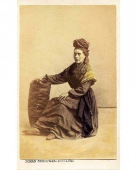 Femme de type gitane, avec turban pour porter le sac posé près d'elle