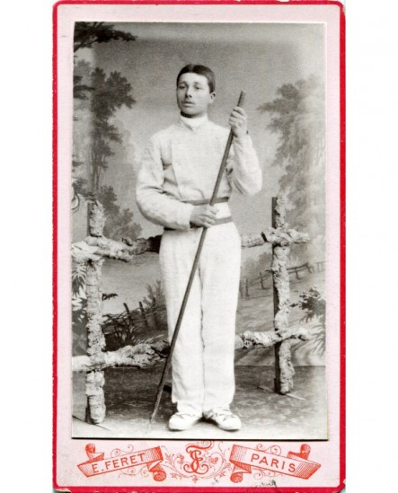 Jeune homme en tenue sportive blanche avec un baton long